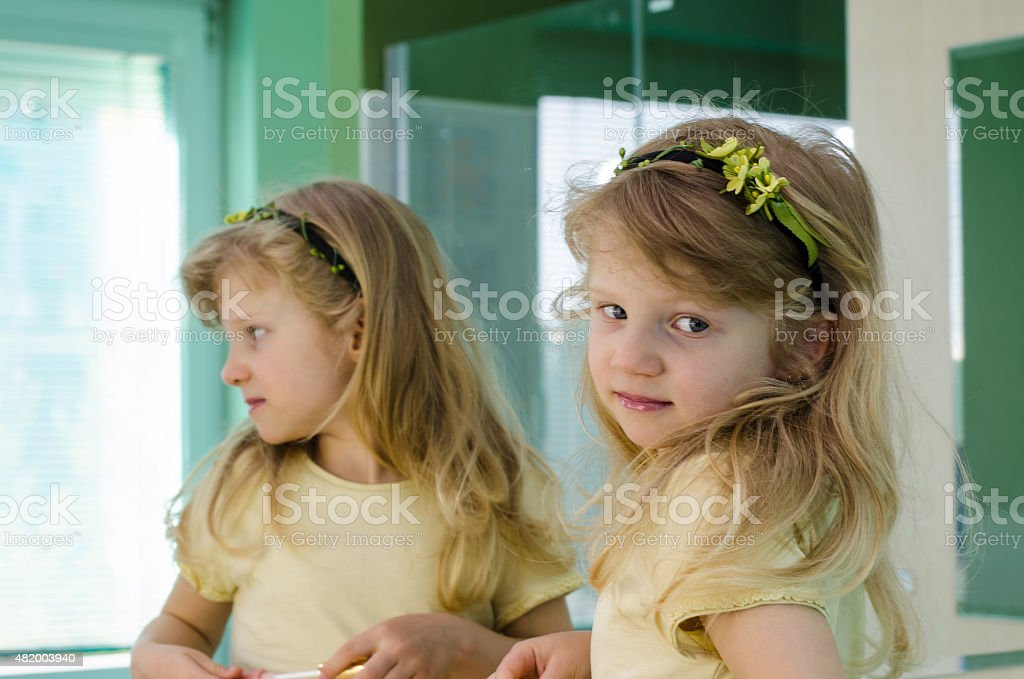 blond girl in front of the mirror stock photo
