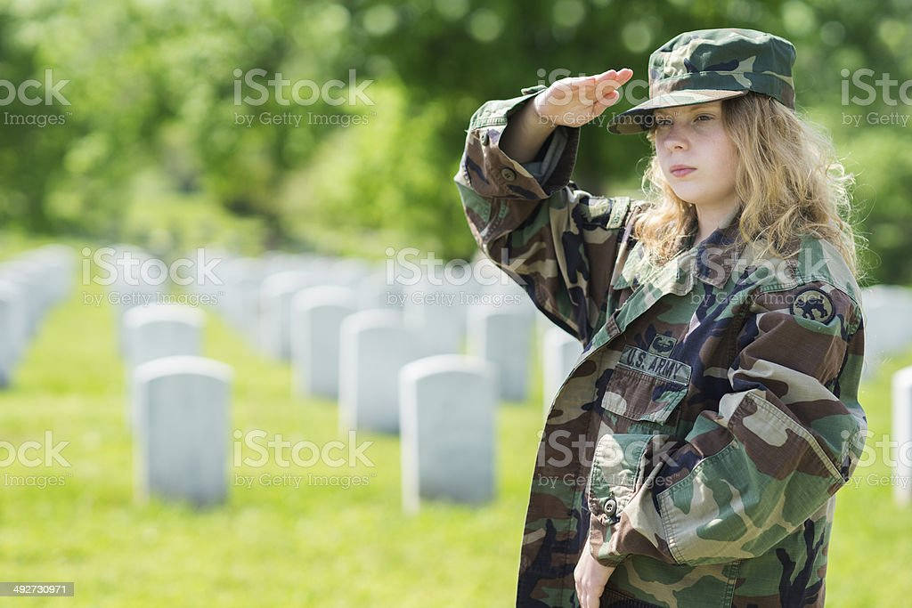 Blond girl in oversized army jacket salutes at military grave stock photo