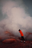 blond girl in red jacket looking at geyser in bolivia
