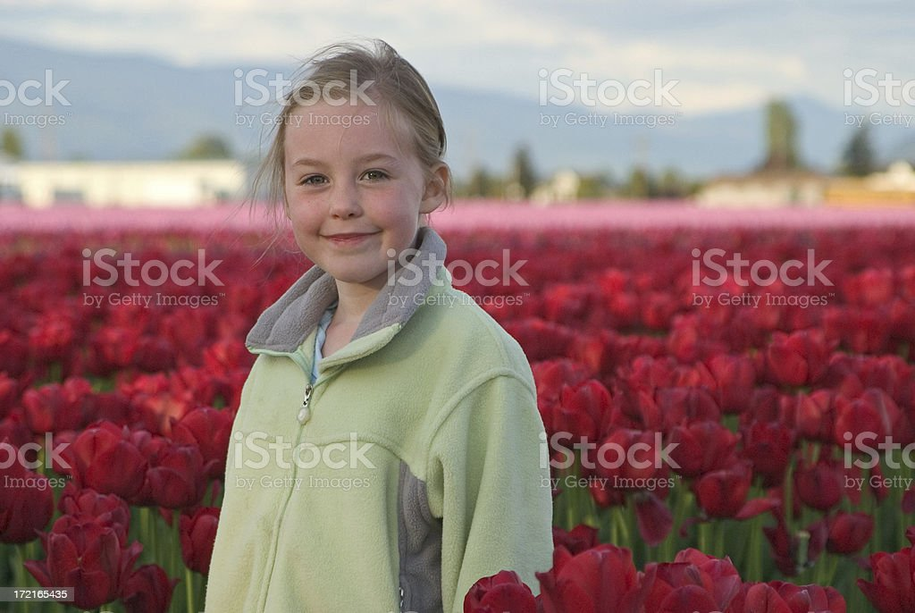 Blond Girl in Red Tulip Field royalty-free stock photo
