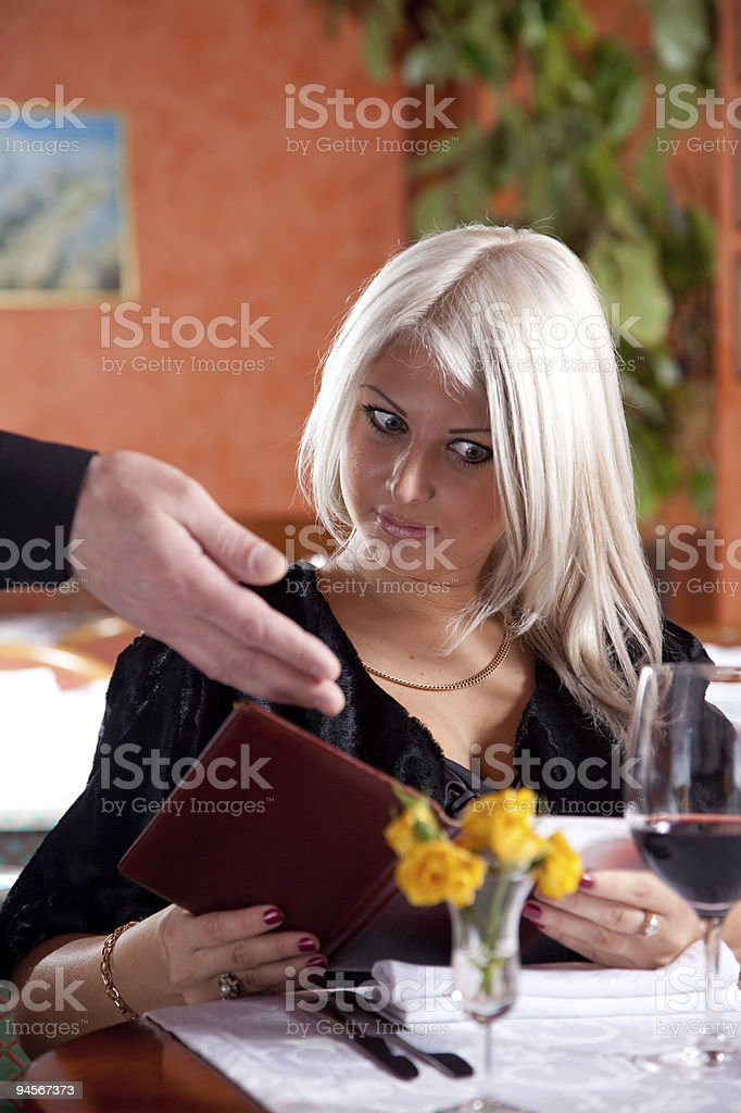Blond girl in  restaurant show a huge bill for food stock photo