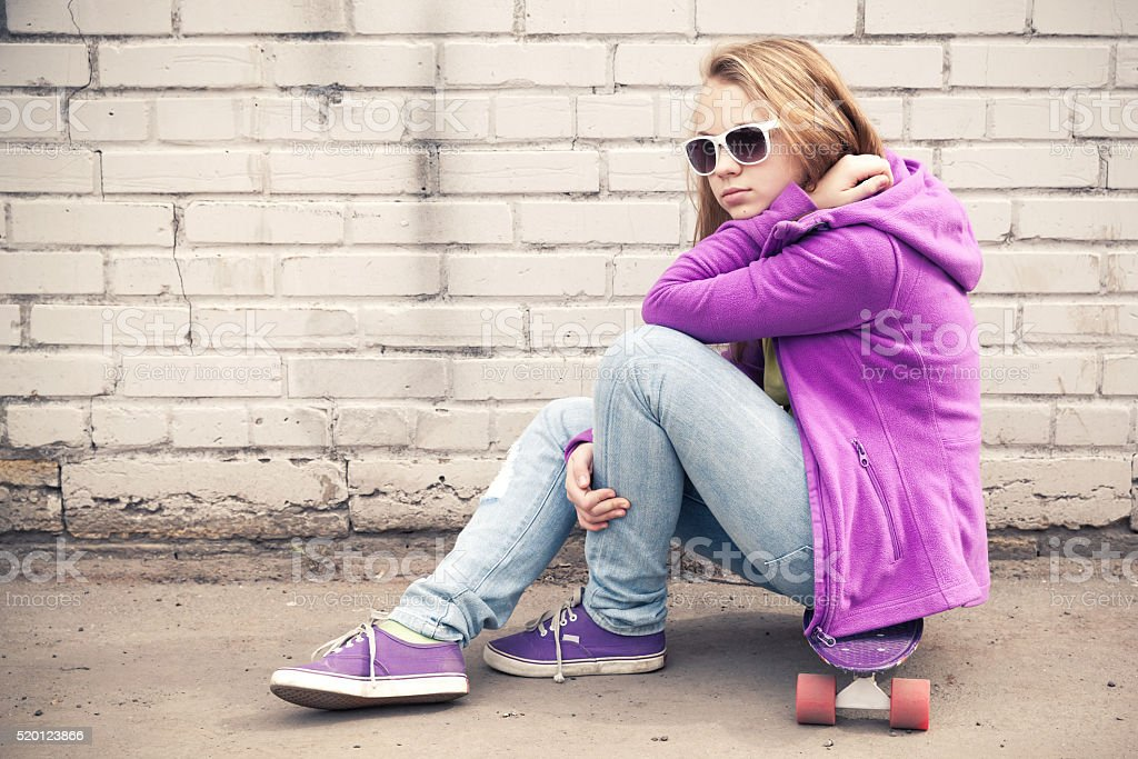 Blond girl in sunglasses sits on her skateboard stock photo