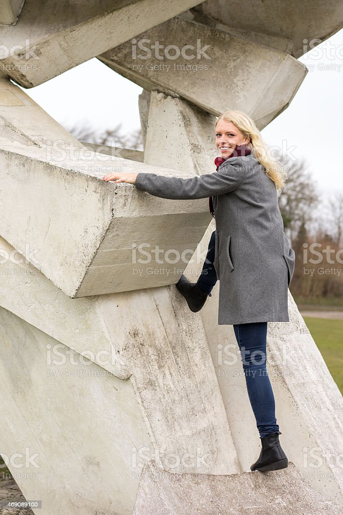 Blond girl in winter coat climbing royalty-free stock photo