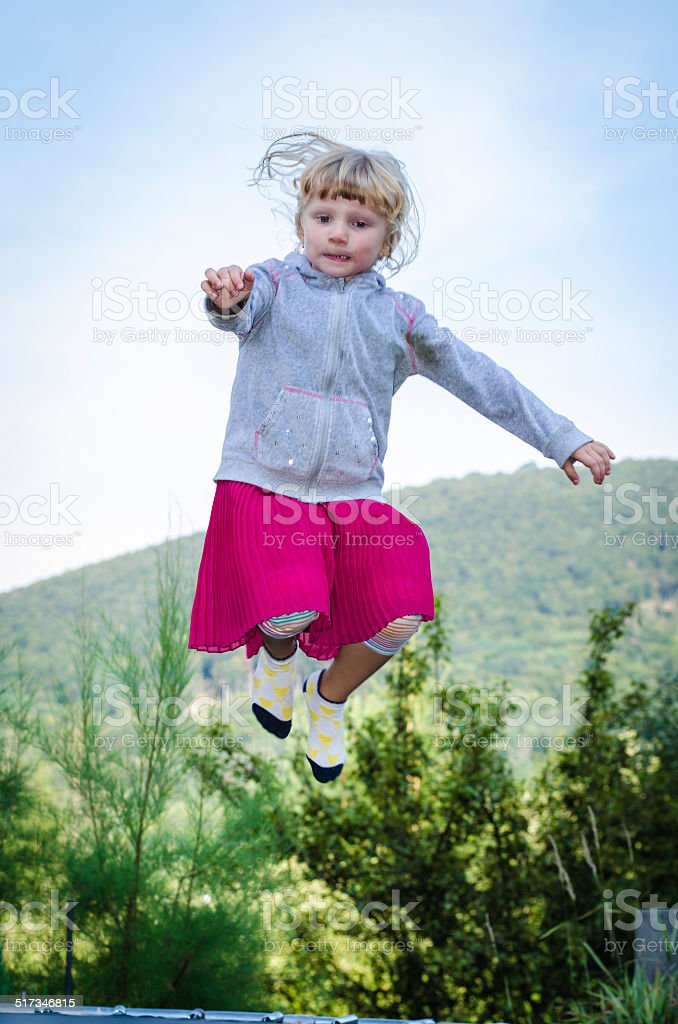 blond girl jumping stock photo