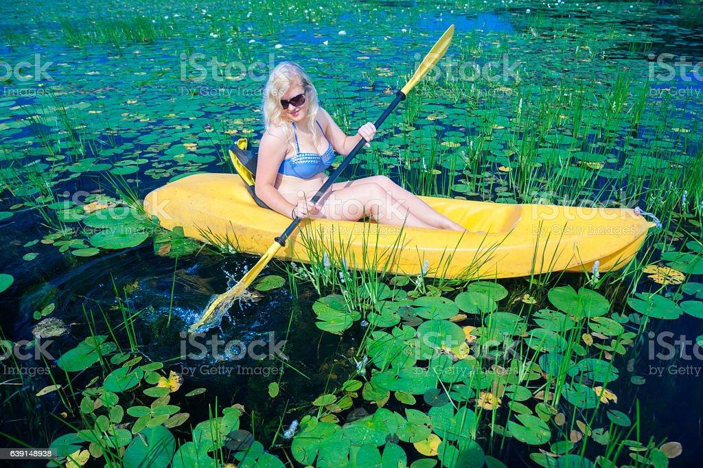 Blond girl kayaking through lilypads stock photo