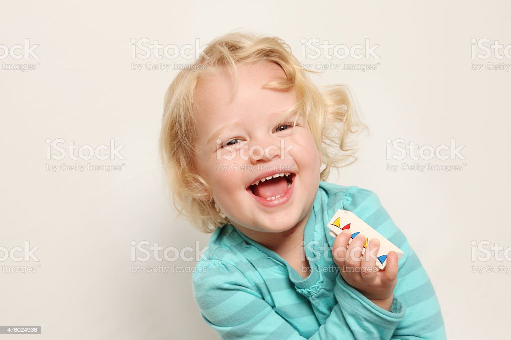 Blond Girl Laughing taken against a beige background stock photo
