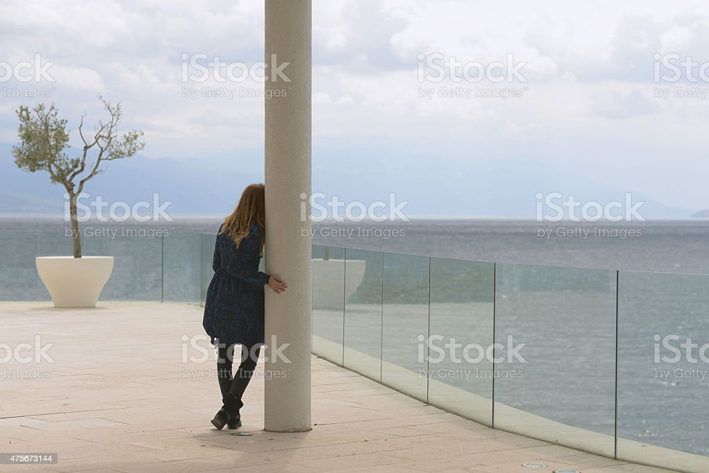 Blond girl looking at the sea next to marbol pillar stock photo