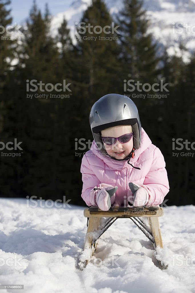 blond girl lying on a sled in the mountains royalty-free stock photo