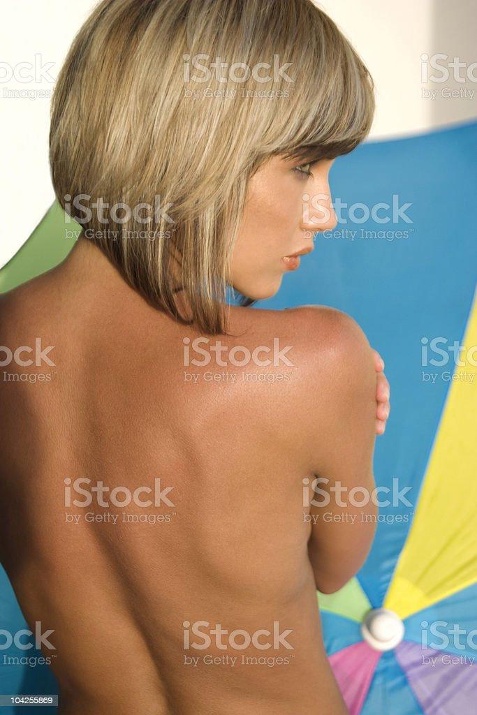 Blond girl next to summer beach umbrella royalty-free stock photo