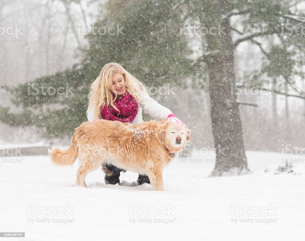 Blond girl petting snowy dog in winter stock photo