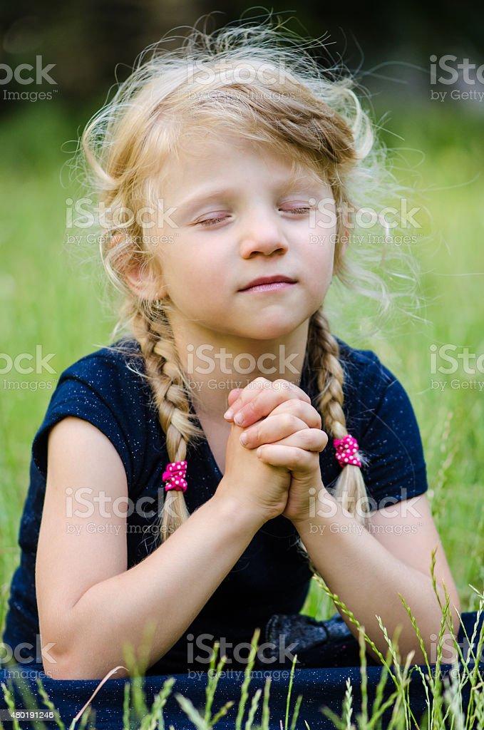blond girl praying stock photo