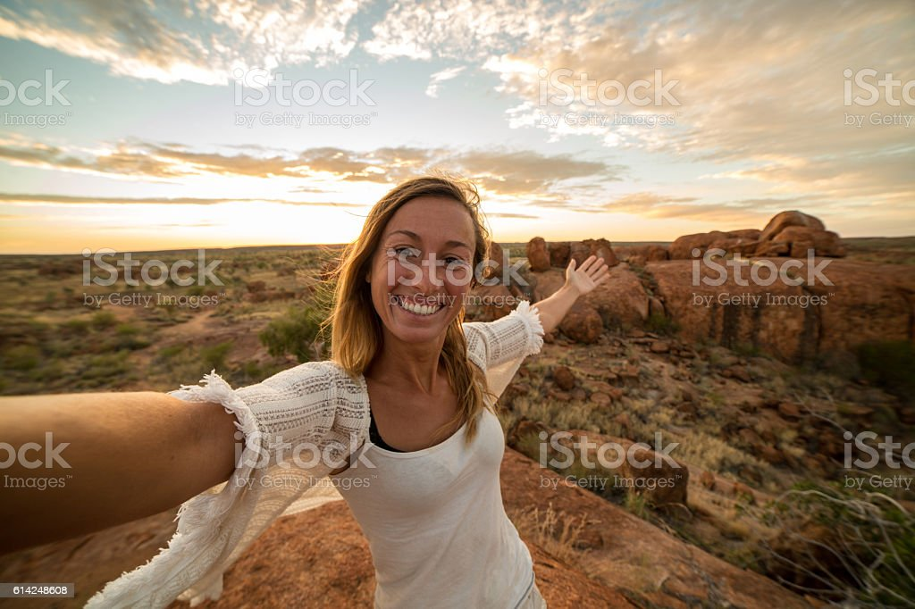 Blond girl takes selfie portrait with spectacular landscape at sunrise stock photo