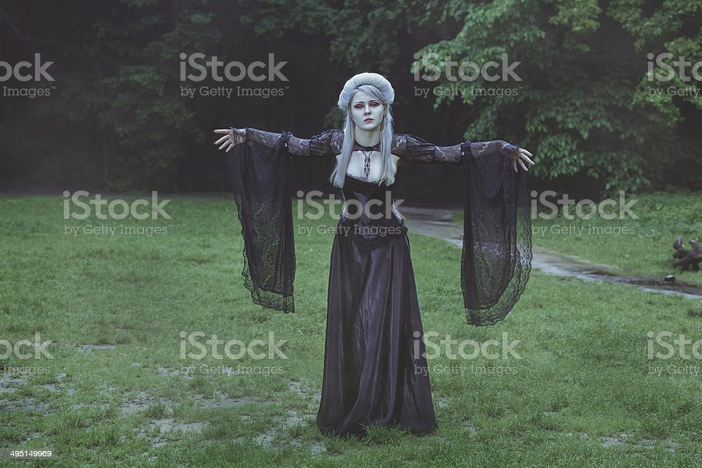 Blond girl with beautiful hair stands in the park. stock photo