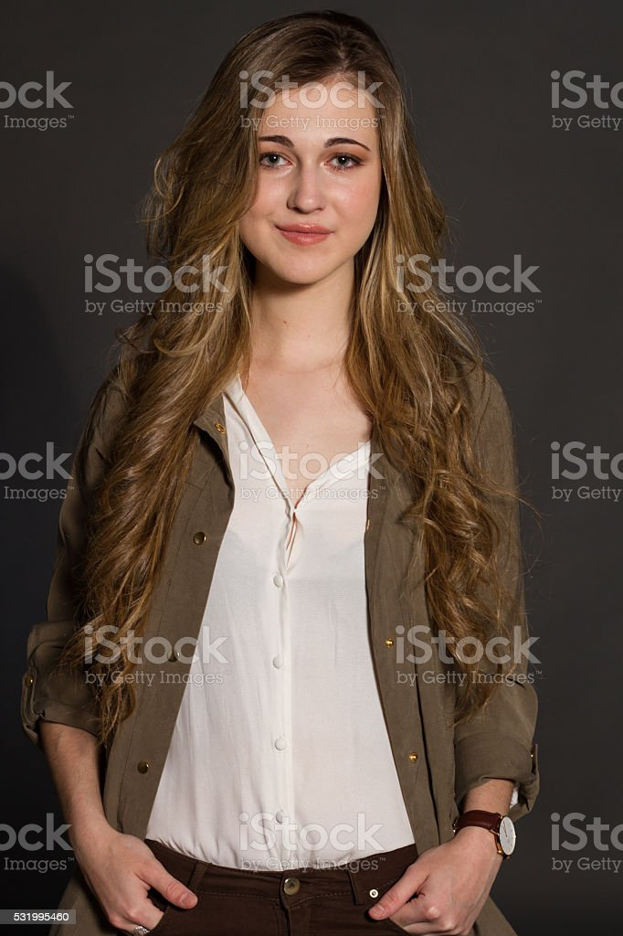 Blond girl with blue eyes on a gray background. stock photo