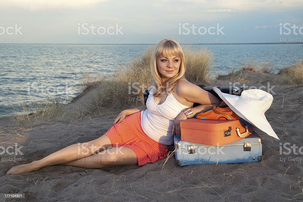 blond girl with her luggage on the beach stock photo