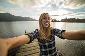 Blond girl woman takes selfie portrait on a wooden pier