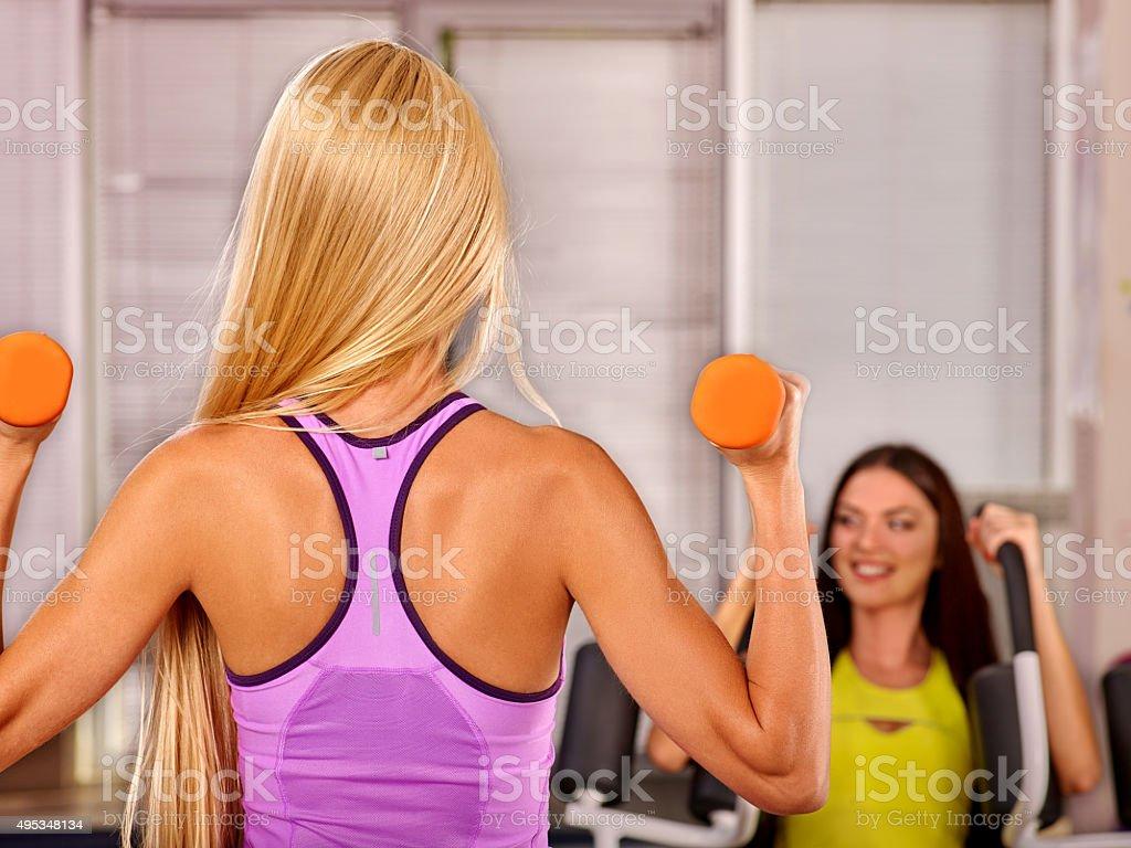 Blond girls holding dumbbells in sport gym stock photo