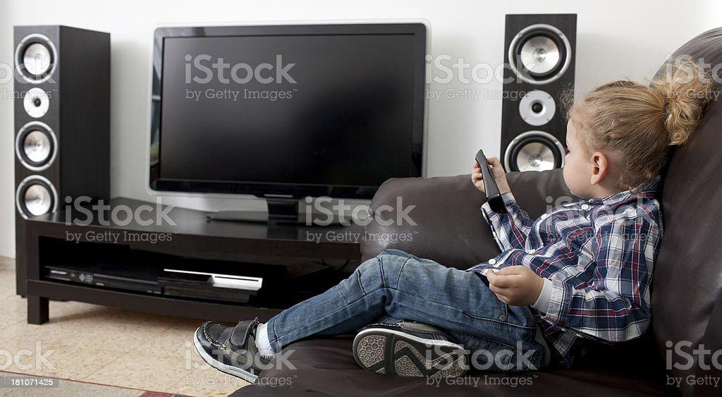Blond hair boy watching TV. stock photo
