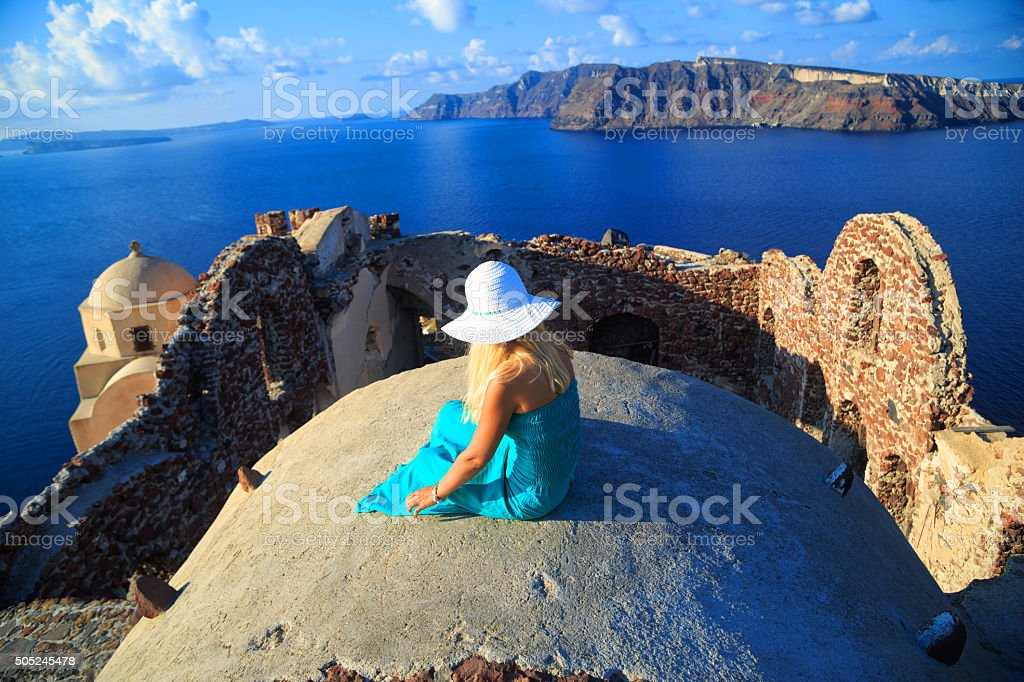 Blond haired woman with turquoise dress in Santorini, Greece. stock photo