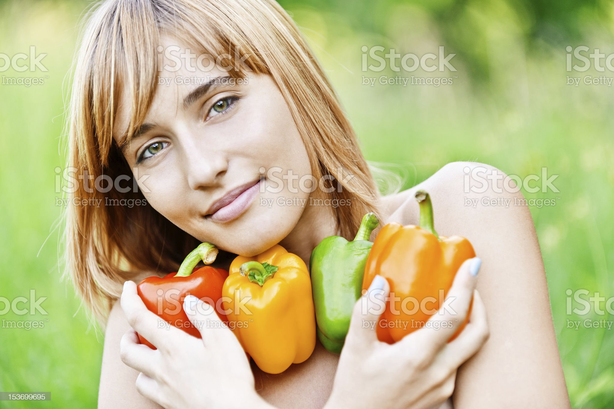 Blond haired young woman clutches four multicolored peppers royalty-free stock photo