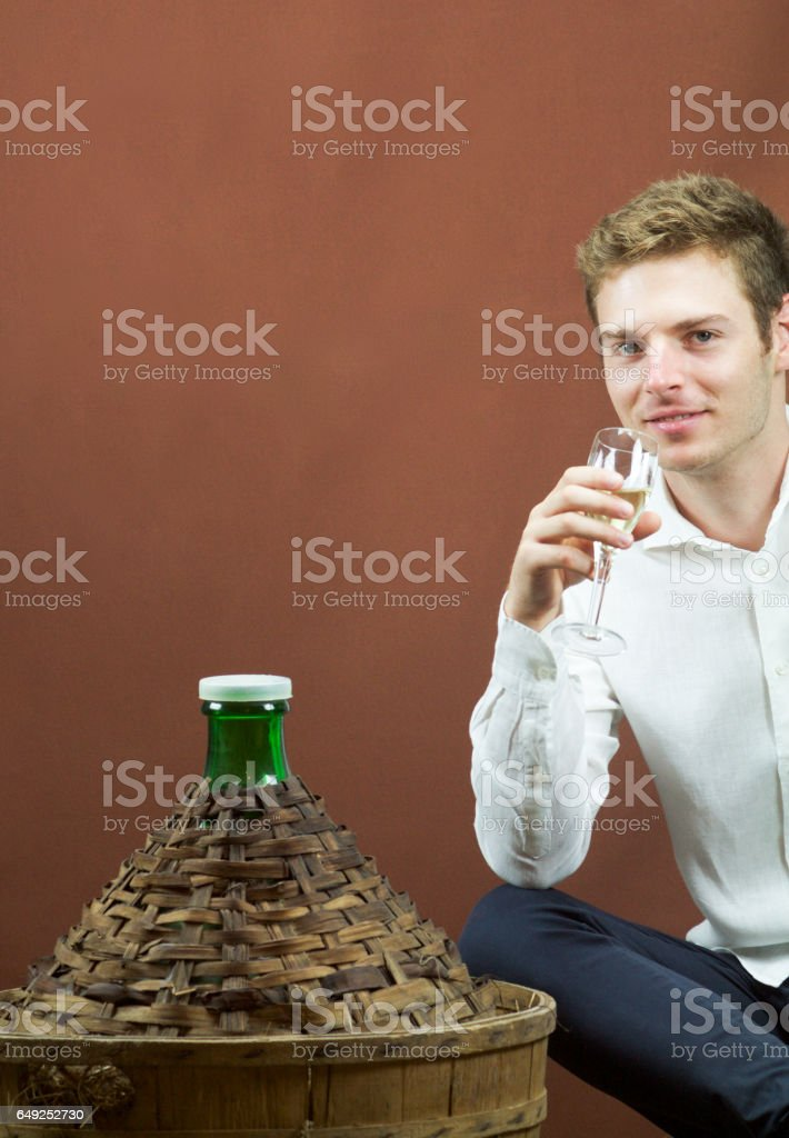 blond handsome men tasting white wine near a carboy. stock photo