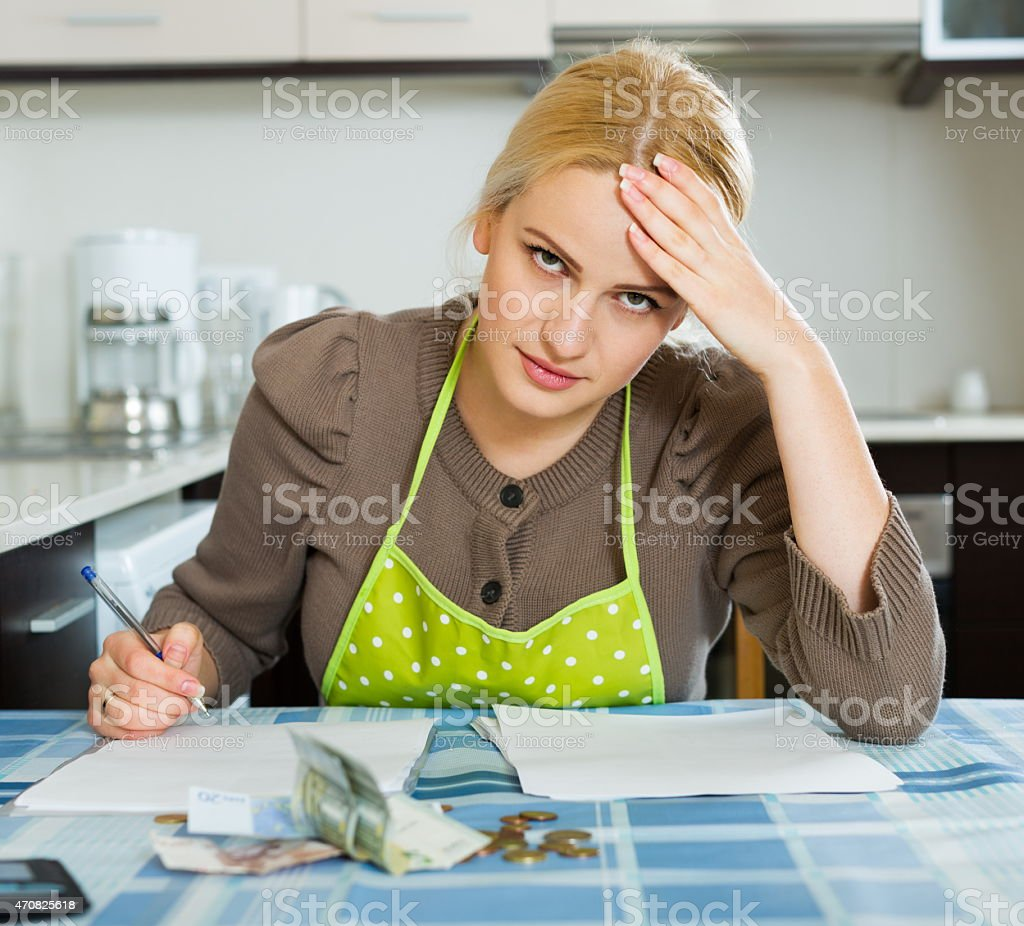 Blond housewife filling payments bills stock photo
