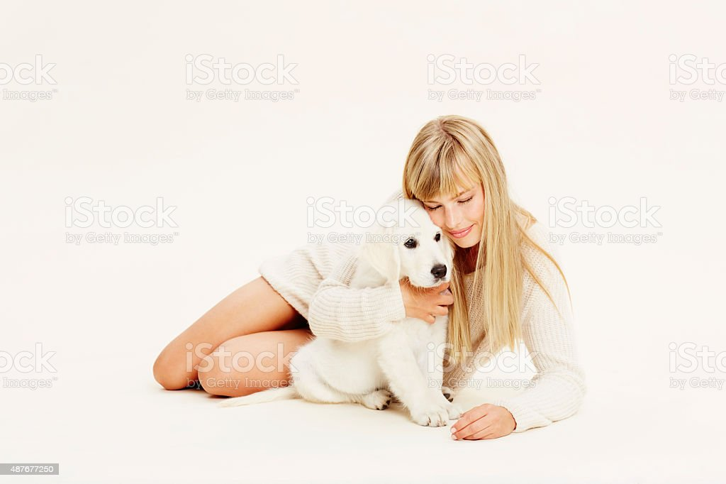 Blond lady embracing puppy stock photo
