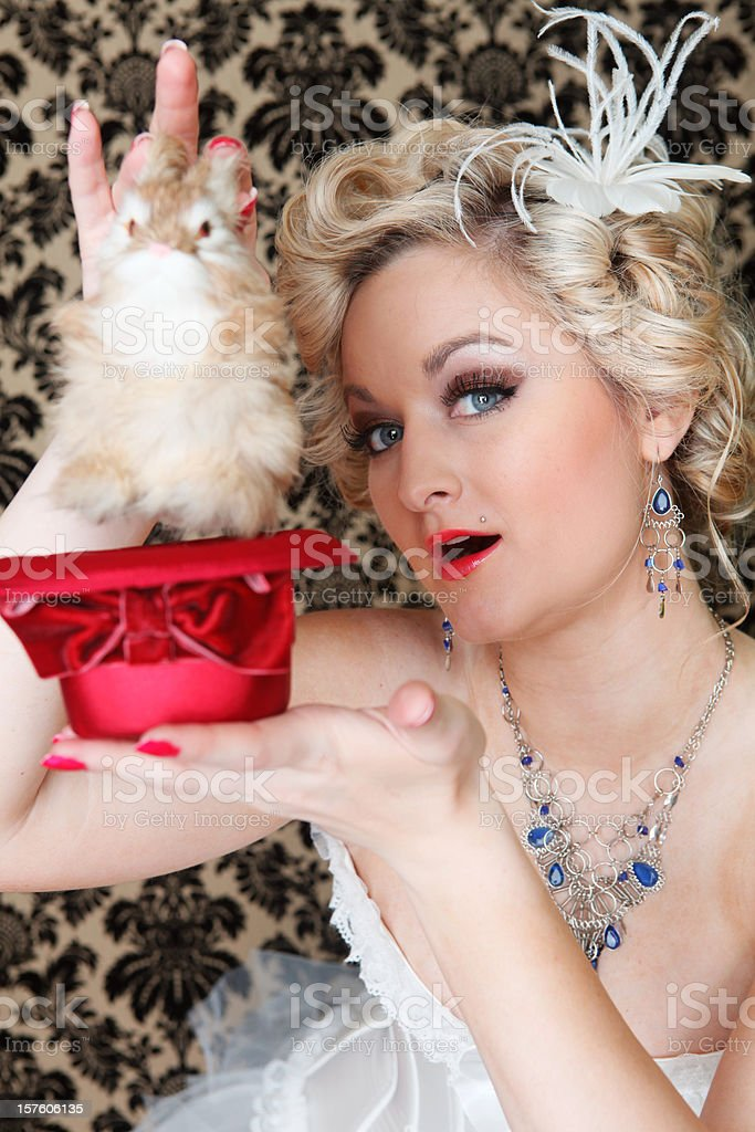 Blond magicians assistant pulling rabbit out of a hat stock photo