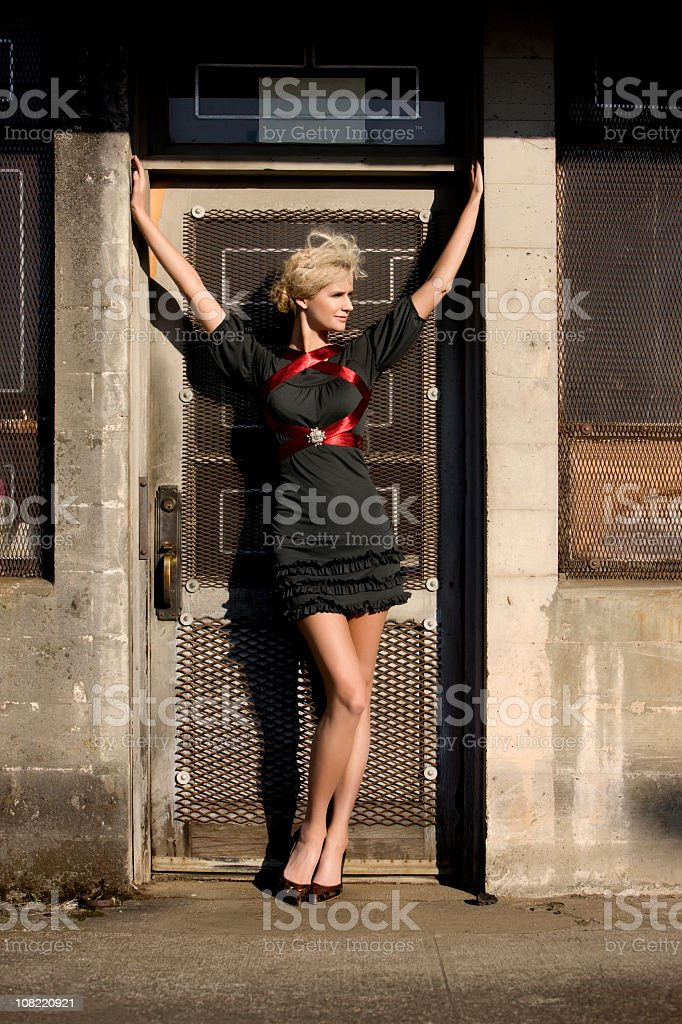 Beautiful Blond Young Woman Fashion Model in Downtown Doorway royalty-free stock photo