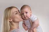 blond mother holding and kissing  baby