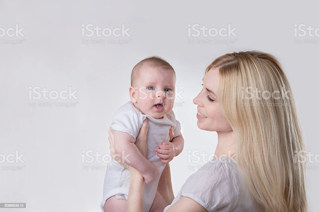 blond mother holding and smiling  baby stock photo
