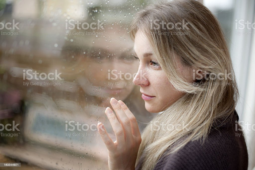 Blond sad girl on the window stock photo