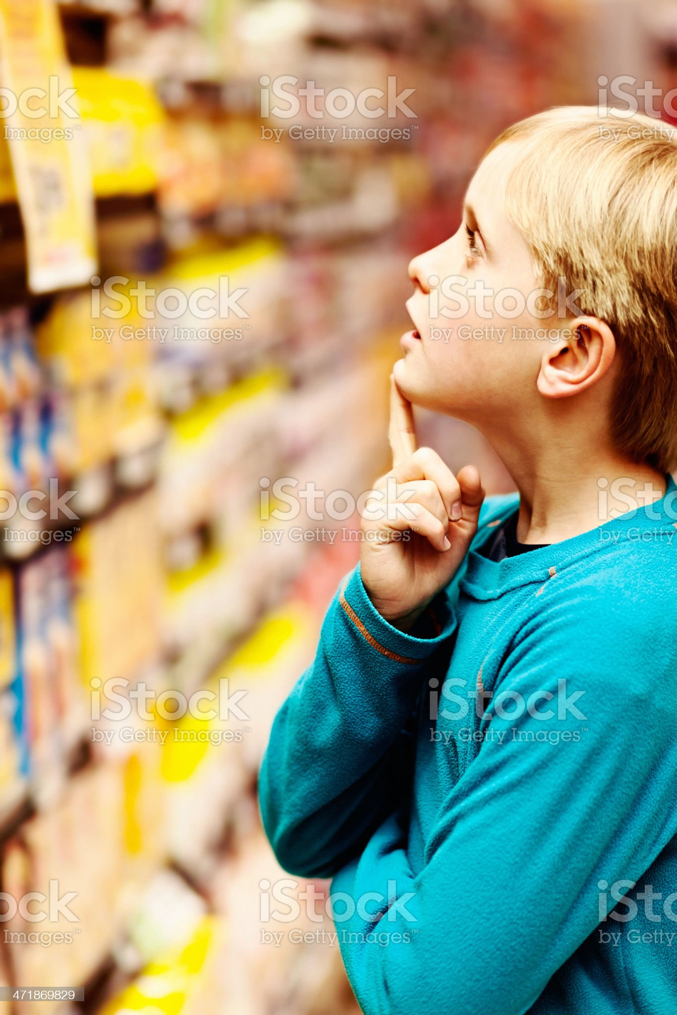 Blond schoolboy deciding what to buy in supermarket royalty-free stock photo