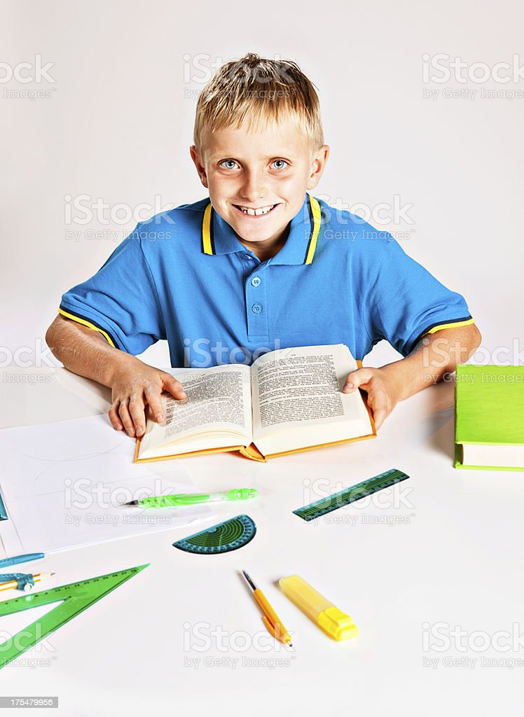 Blond schoolboy enjoying his schoolwork stock photo