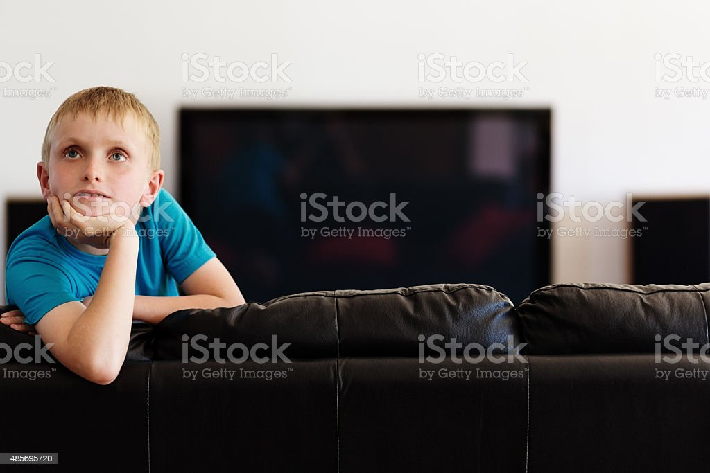 Blond schoolboy leaning over back of couch, thinking stock photo
