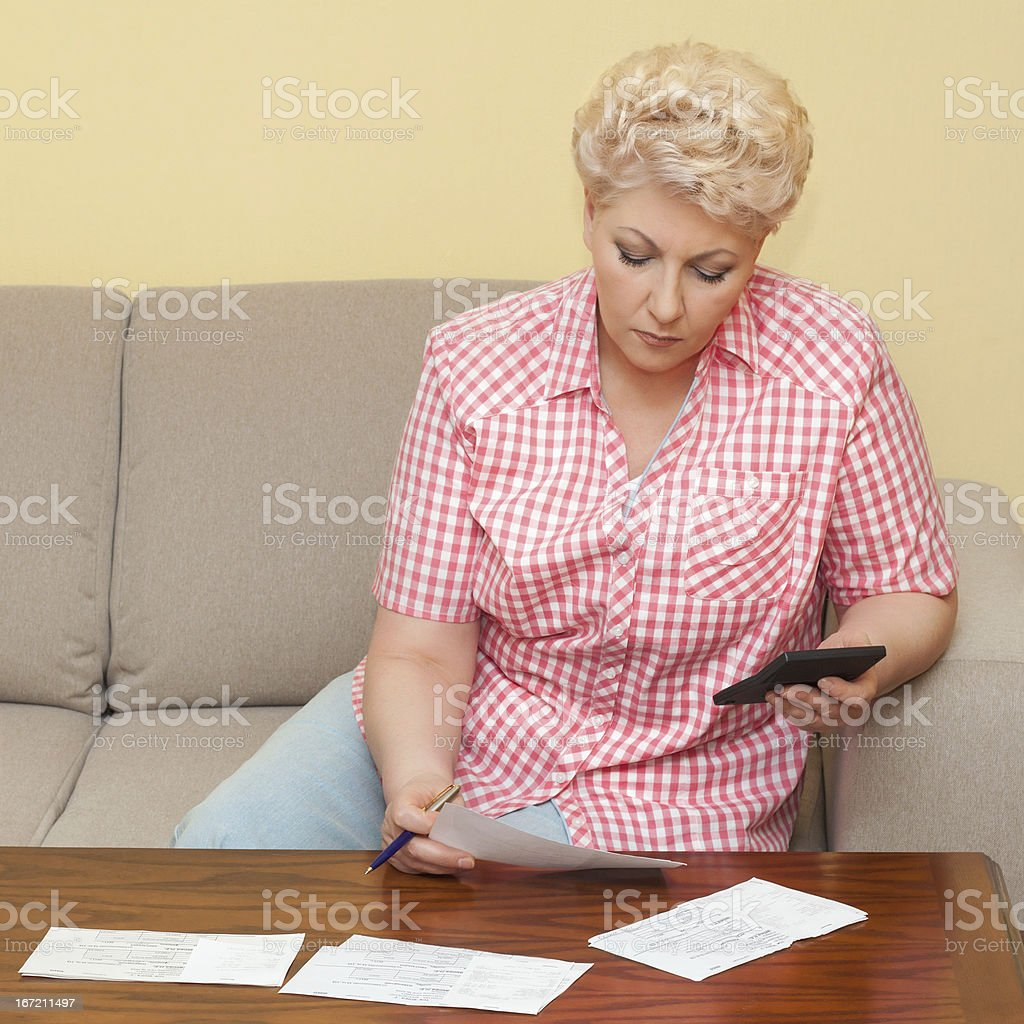 blond senior calculating her debts royalty-free stock photo