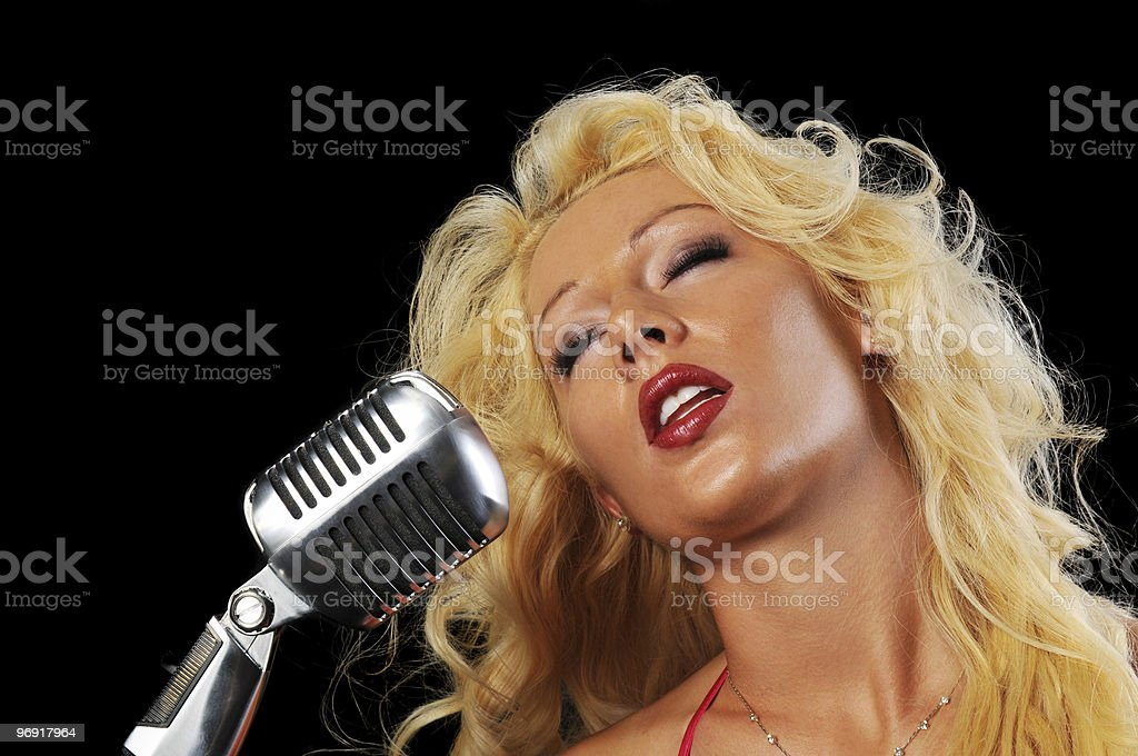 Blond singer on vintage microphone stock photo