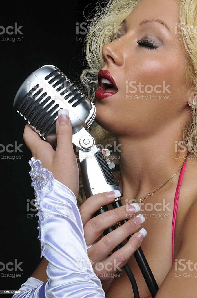 Blond singer on vintage microphone royalty-free stock photo
