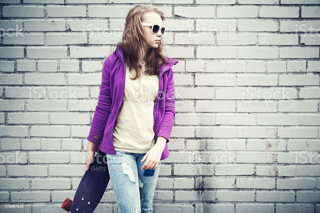 Blond teenage girl in jeans and sunglasses holds skateboard stock photo