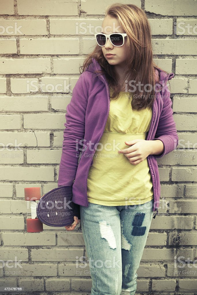 Blond teenage girl in jeans and sunglasses with skateboard stock photo