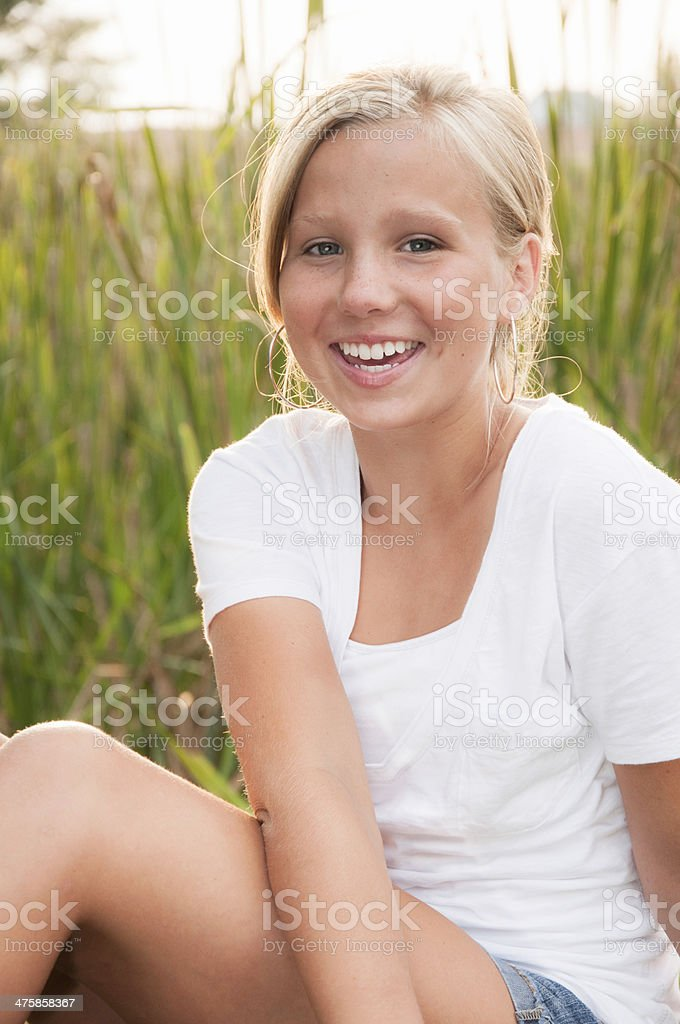 Blond Teenage Girl Laughing Outdoors by Tall Grass stock photo