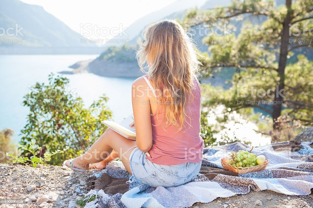 Blond teenager girl sitting on a cover, picnic, mountains stock photo