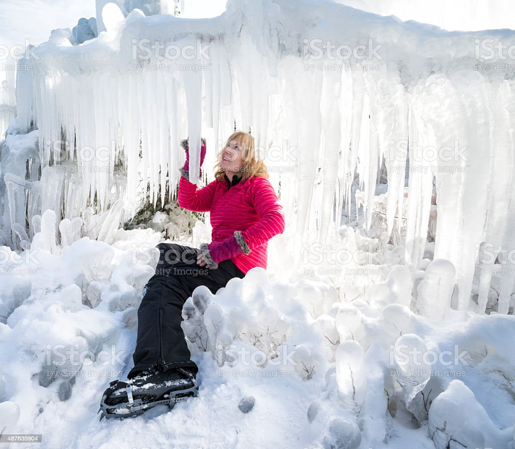 Blond woman admires giant icicles stock photo