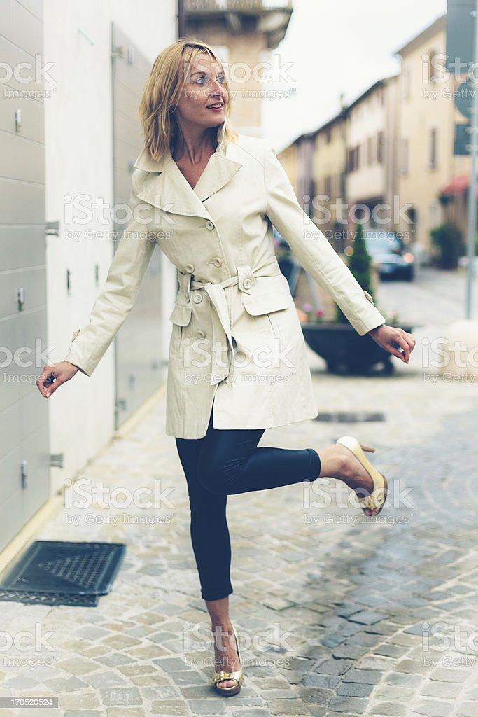 Blond woman, balancing on golden heels stock photo