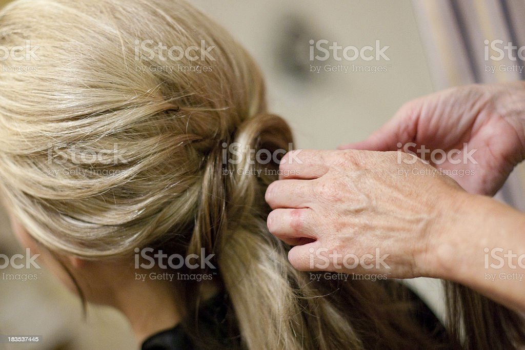 blond woman bride having hair done styled by a stylist stock photo
