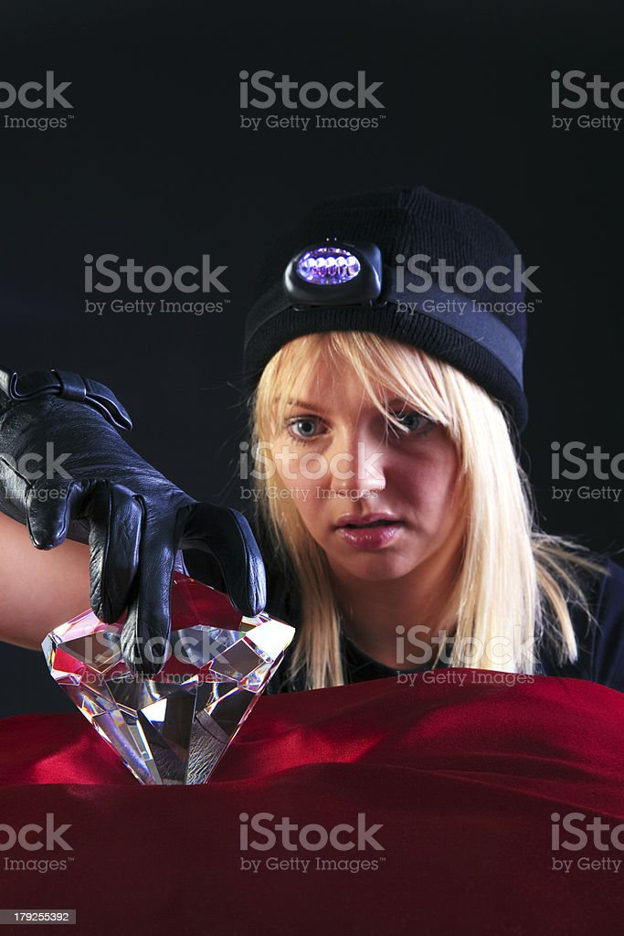 Blond woman cat burglar stealing a large diamond royalty-free stock photo