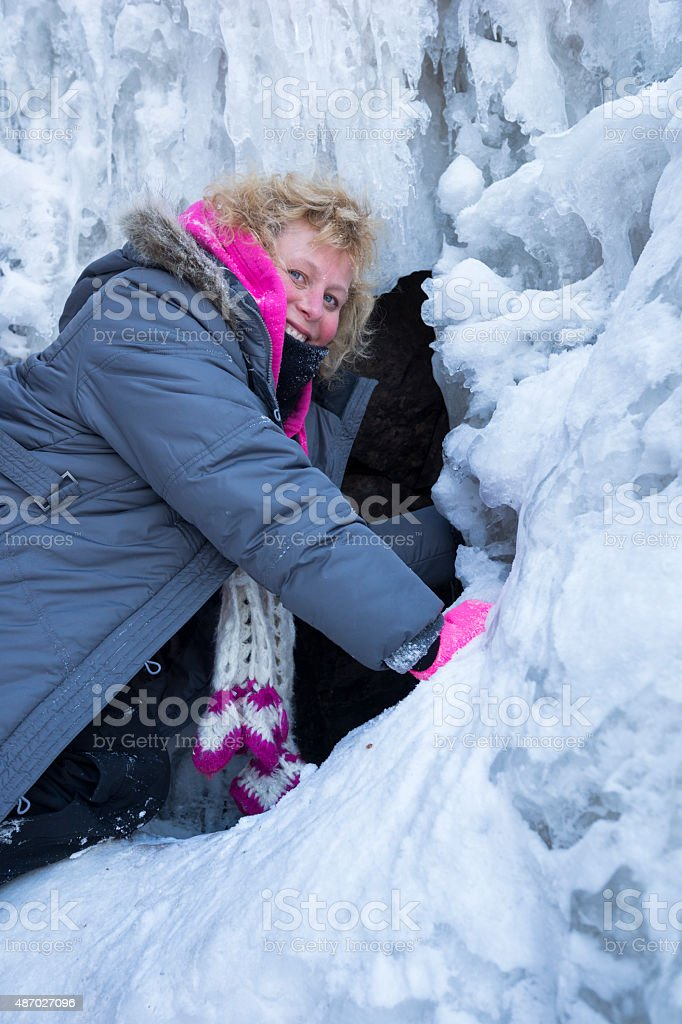 Blond woman climbs frozen waterfall at Gooseberry Falls State Park stock photo