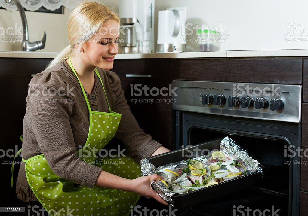 Blond woman cooking fish stock photo