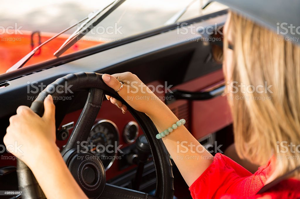 Blond woman drives convertible vehicle in summer. stock photo