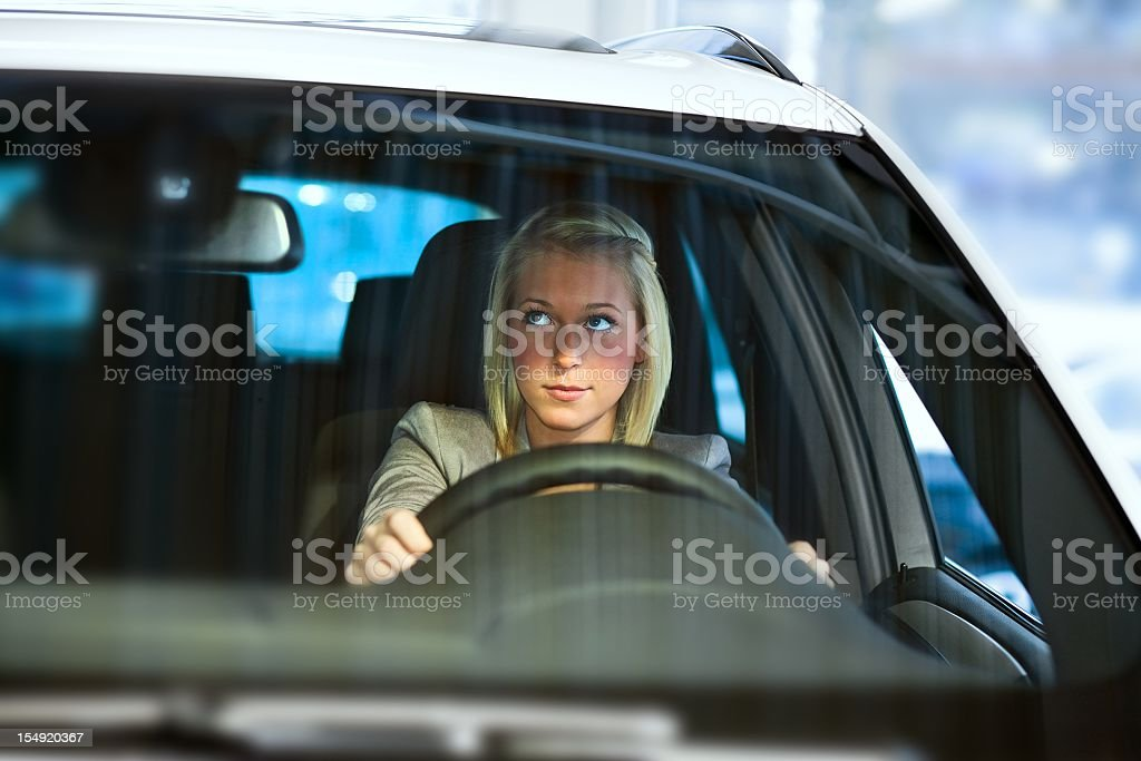 blond woman driving a car (looking in the mirror) stock photo